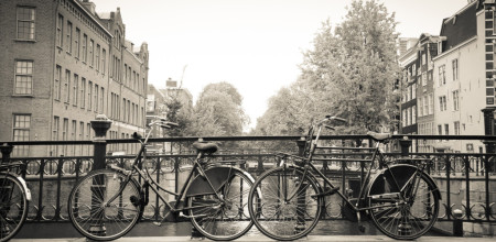 Couples of old black bikes in a bridge over the canal in Amsterdam.
